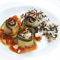 Oven-baked eggplant and zucchini rolls with feta cheese and tomato sauce, served with rice and wild rice,