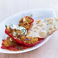 Long bell peppers stuffed with couscous braised in tomato sauce, served with yogurt and pappadams,