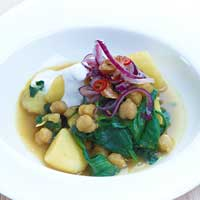 Potatoes and chickpeas in a curry and spinach sauce with spicy onions,