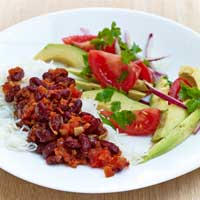 Kidney beans in spicy tomato sauce with rice and avocado and tomato salad ,