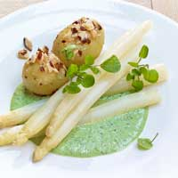 White asparagus with green sauce and potatoes in almond butter,