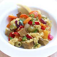 Oven-baked paella risotto with seitan, bell peppers, and olives,